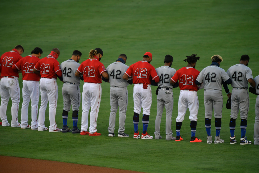 Players on the Angels and Seattle Mariners lock arms on the field during the national anthem.