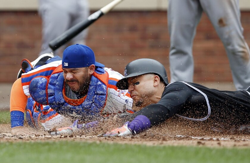 New York Mets catcher Rene Rivera, left, tags out Colorado Rockies' Carlos Gonzalez, right, after Gonzalez tried to score on a wild pitch during the fifth inning of a baseball game, Sunday, July 31, 2016, in New York. (AP Photo/Kathy Willens)