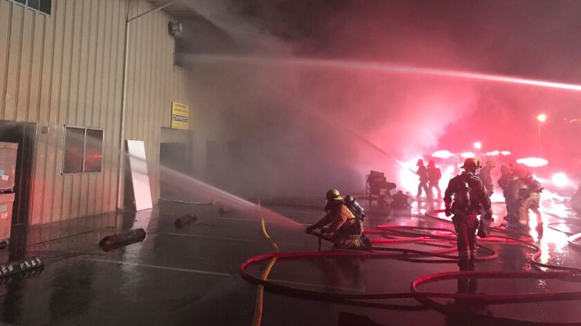 Firefighters work to put out a three-alarm fire at a building in Goleta, Calif.