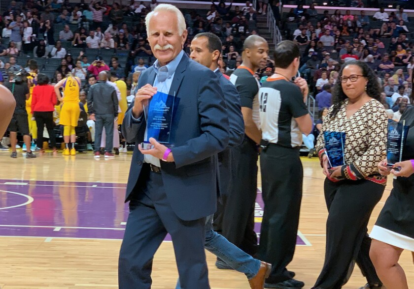 Corona del Mar High cross-country and track and field coach Bill Sumner received an award for leadership in the field of sports and coaching at halftime of the Los Angeles Sparks game on Thursday at Staples Center in Los Angeles.