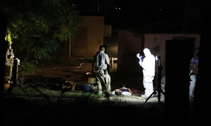 Crime scene investigators work in Ciudad Juarez, Mexico, at the site where several people, including a young girl, where killed during a party celebrating a baseball victory.