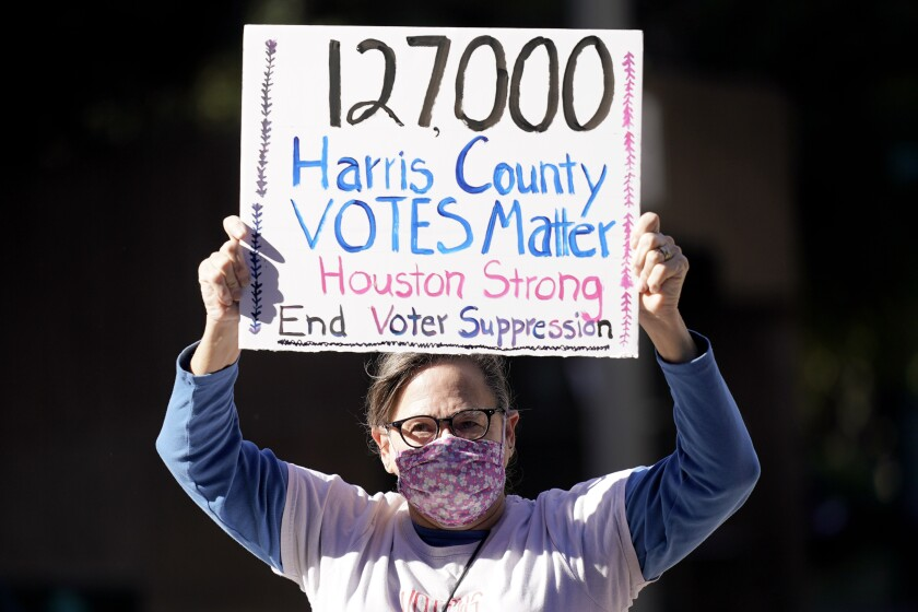 """Gina Dusterhoft holds up a sign reading in part, """"Harris County Votes Matter."""""""