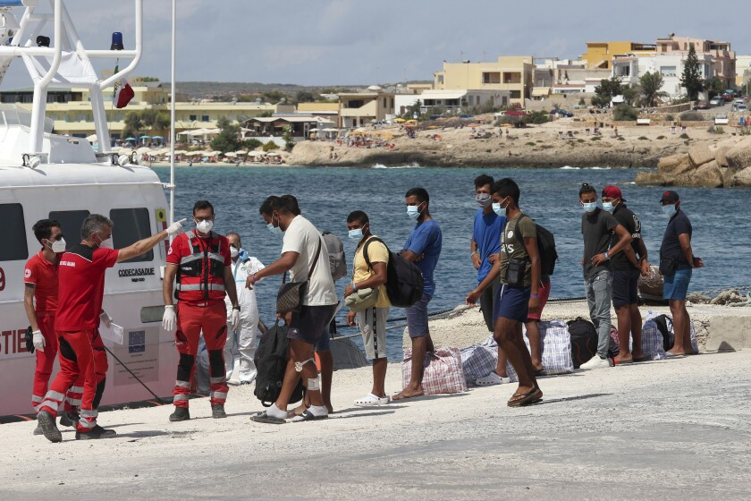Migrants wait to board a coast guard ship that will take them to the GNV Rhapsody ferry moored off Lampedusa island, Italy, Saturday, Sept. 5 , 2020. Italian officials have been hastily chartered ferries and put other measures into place to fight severe overcrowding at migrant centers on the tiny island of Lampedusa. (AP Photo/Mauro Seminara)