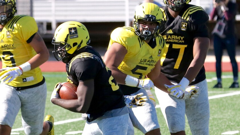 Defensive lineman Marlon Tuipulotu (51) of Independence Central in Oregon chases after running back Eno Benjamin during a West team practice leading up to the U.S. Army All-American Bowl in San Antonio.