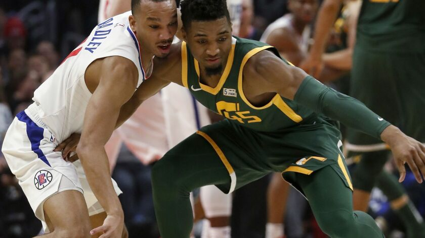 LOS ANGELES, CALIF. - JAN. 16, 2019. Clippers guard Avery Bradley slaps the ball away from Jazz guar