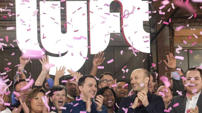 Lyft co-founders John Zimmer, left, and Logan Green cheer as they ring a ceremonial opening bell in