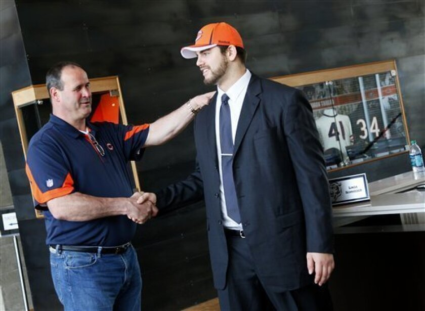 Chicago Bears first round draft choice Gabe Carimi, right, meets with offensive line coach Mike Tice in the lobby of Halas Hall on Saturday, April 30, 2011 in Lake Forest, Ill.(AP Photo/Charles Cherney)
