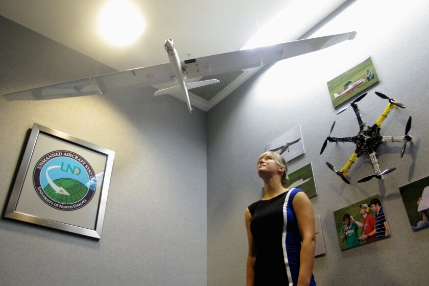In this Sept. 29, 2015 photo, University of North Dakota student Megan Halek stands in the lobby of the Grand Forks school's aviation department in Grand Forks, N.D. Halek recently aced a training program to fly the Predator drone flown by U.S. Customs and Border Protection, but she doesn't meet wh
