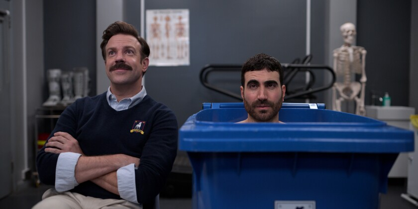 """Jason Sudeikis and Brett Goldstein, one in a chair, the other in a trash bin, sit next to each other in """"Ted Lasso."""""""