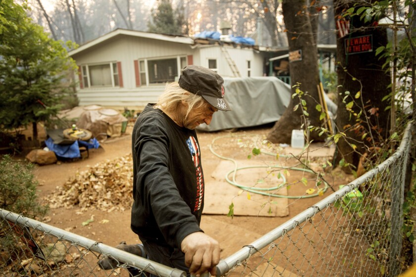 Jimmy Clements, who stayed at his home as the Camp fire raged through Paradise, Calif., leans against his fence.