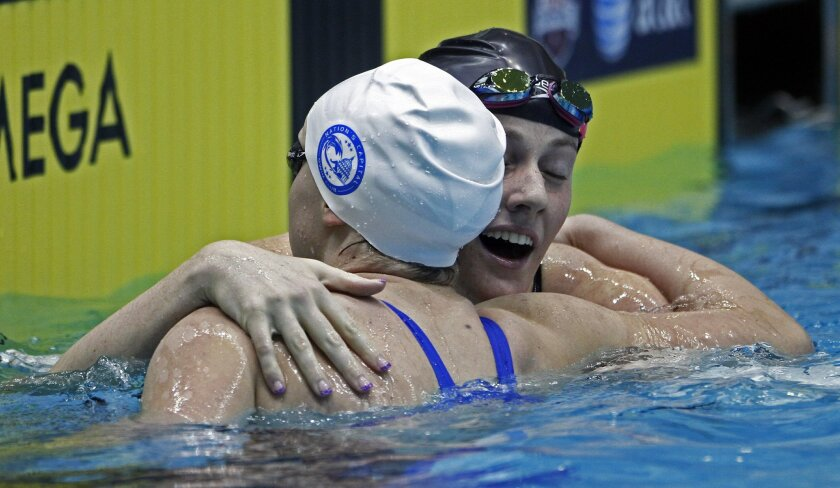 Katie Ledecky, left, gets a hug from Missy Franklin after competing in the women's 500-yard freestyle race during final round at the Winter National swimming championships at Allan Jones Intercollegiate Aquatic Center on Thursday, Dec. 5, 2013, in Knoxville, Tenn. (AP Photo/Wade Payne)