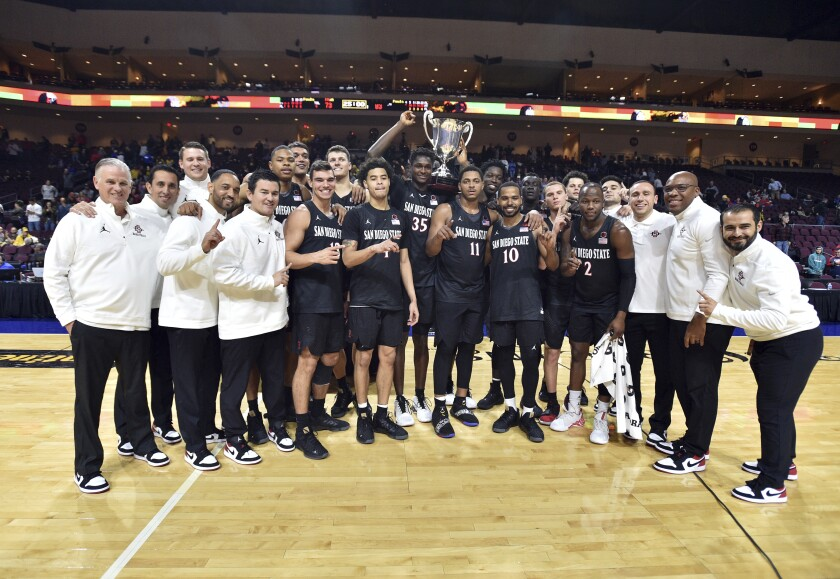 San Diego State celebrate with the Las Vegas Invitational championship trophy after defeating Iowa in an NCAA college basketball game Friday, Nov. 29, 2019, in Las Vegas. (AP Photo/David Becker)