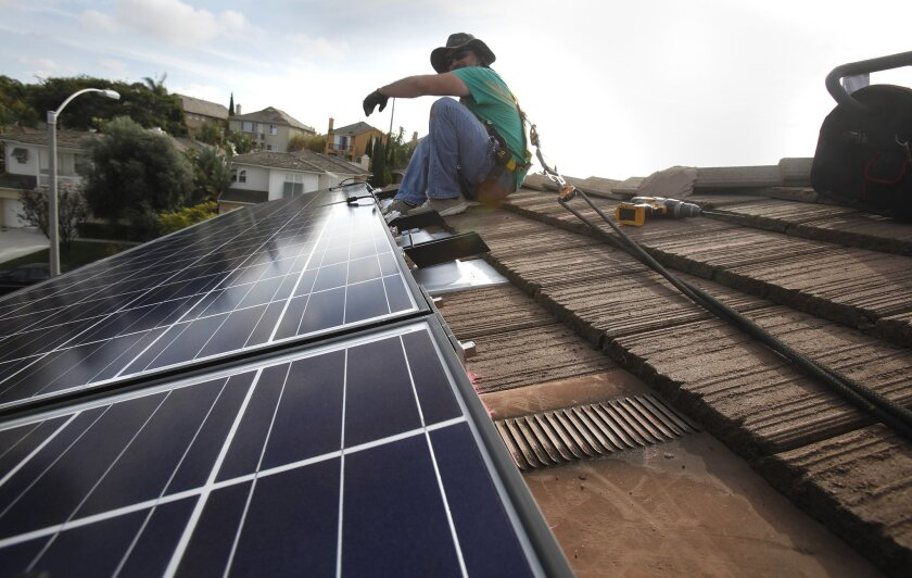 Armando Flores, an installer with SolarCity takes a break while installing panels in Torrey Hills.