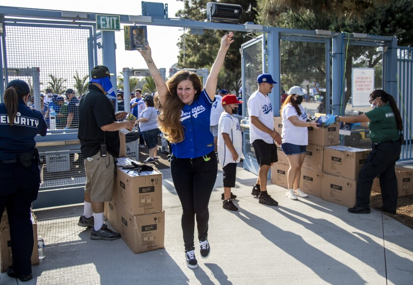 A smiling woman holds her hands high as she enters Dodger Stadium.