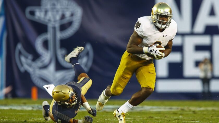 Notre Dame running back Dexter Williams escapes the grip of Navy linebacker Elan Nash on Saturday at SDCCU Stadium.