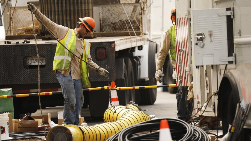 Department of Water and Power crews block South Westmoreland Avenue at 6th Street in Koreatown as they work to restore power to customers Monday.