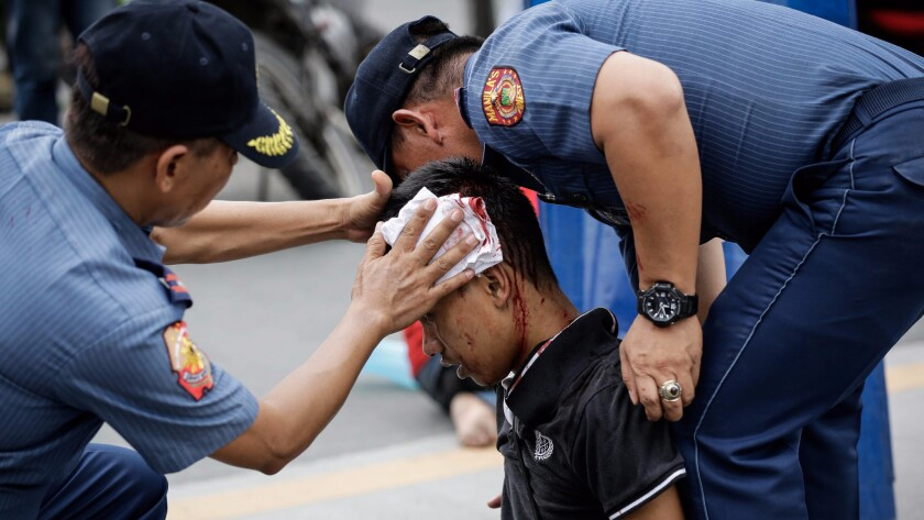 Police officers help an injured protester during a rally in front of the U.S. Embassy in Manila, Philippines. A police van rammed into protesters, injuring several.