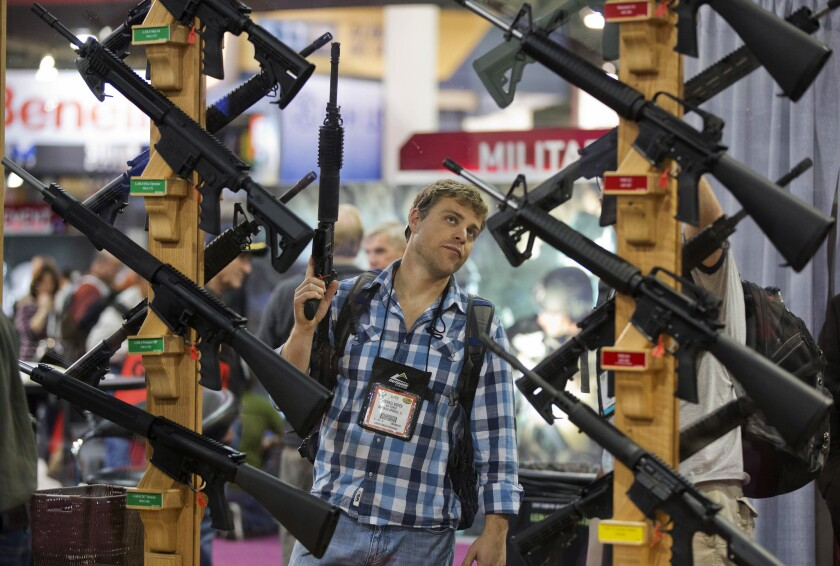 In this Jan. 17, 2013, file photo, Michael Kiefer, of DeFuniak Springs, Fla., checks out a display of rifles at the Rock River Arms booth during the 35th annual SHOT Show in Las Vegas. The largest gun industry trade show will be taking place in Las Vegas Jan. 23-26 just a few miles from where a gunman carried out the deadliest mass shooting in modern U.S. history.