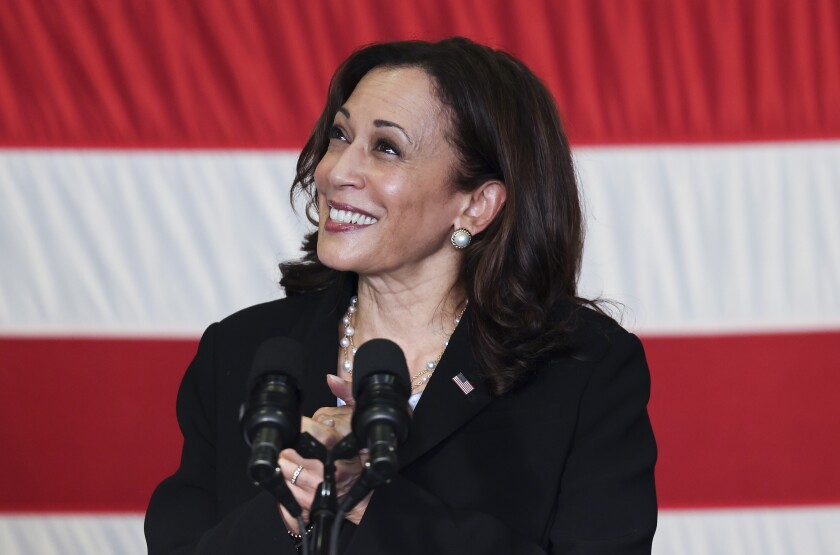 Kamala Harris speaks into a microphone with the U.S. flag in the background