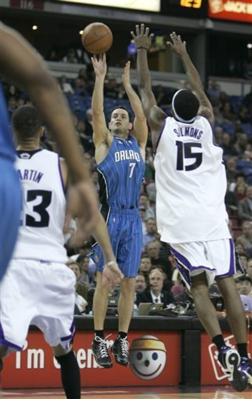 Orlando Magic guard J.J. Redick,  takes a 3-point shot over Sacramento Kings' John Salmons, right, and Kevin Martin, left,  during the first quarter of an NBA basketball game in Sacramento,  Calif., Tuesday, Jan. 13, 2009.  The Magic made 23 3-point shots to set an NBA record in their 139-107 victo