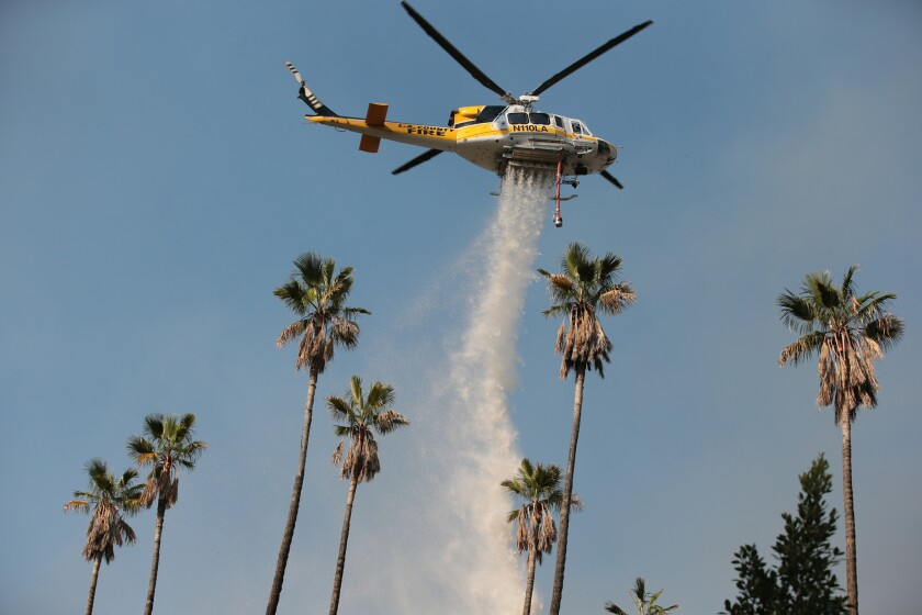 An L.A. County Fire Department helicopter drops water on the Colby fire above Glendora in January. The department and other agencies are bracing for fire weather this week.