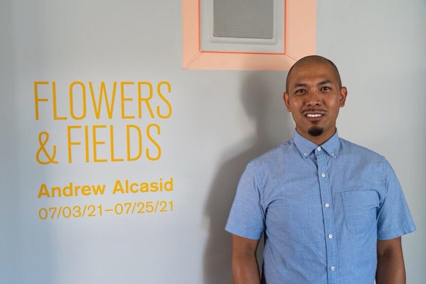 """San Diego artist Andrew Alcasid poses in front of his latest exhibition, """"Flowers & Fields"""""""