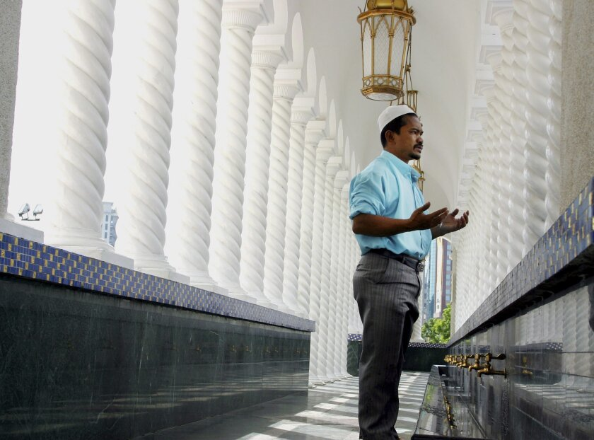 FILE - In this July 28, 2002 file photo, a Muslim man prays as he enters Sultan Omar Ali Saifuddien Mosque in Bandar Seri Begawan, Brunei. Brunei on Thursday, May 1, 2014 embraced a form of Islamic Shariah criminal law that includes harsh penalties, a move slammed by international rights group as a