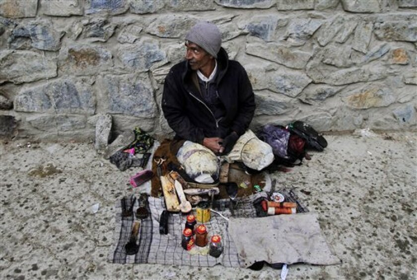 An Afghan shoe polisher waits for customers in the center of Kabul, Afghanistan, Thursday, March 14, 2013. (AP Photo/Ahmad Jamshid)