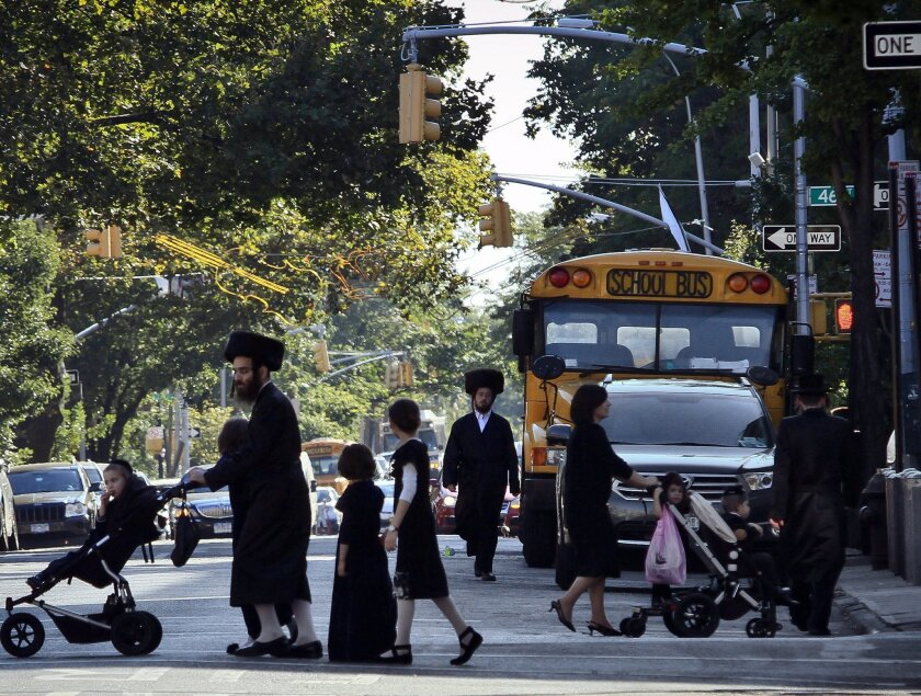 FILE - In this Sept. 20, 2013 file photo, children and adults cross a street in front of a school bus in Borough Park, a neighborhood in the Brooklyn borough of New York that is home to many ultra-Orthodox Jewish families. Critics have charged for years that the rudimentary level of secular education at private yeshiva schools serving New York's Hasidic communities are deficient in teaching science, geography and math to grade school students. Now, for the first time, the city Department of Education is investigating more than three dozen of the schools to make sure their instruction is up to the most basic standards. (AP Photo/Bebeto Matthews, File)