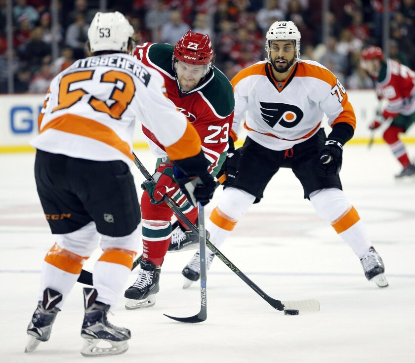New Jersey Devils right wing Bobby Farnham, center, shoots as Philadelphia Flyers defenseman Shayne Gostisbehere (53) and right wing Pierre-Edouard Bellemare (78), of France, defend during the second period of an NHL hockey game, Tuesday, Feb. 16, 2016, in Newark, N.J. (AP Photo/Julio Cortez)