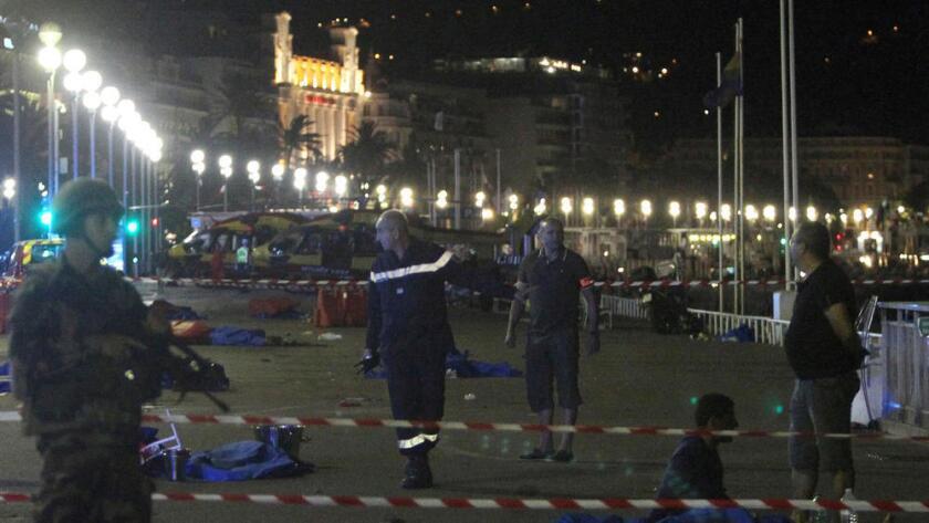Soldados, policías y bomberos caminan cerca de los cuerpos cubiertos con frazadas azules en la ciudad de Niza, Francia.