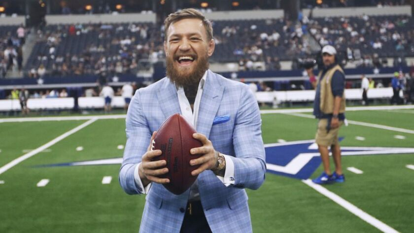 UFC fighter Conor McGregor reacts on the sideline before an NFL football game between the Dallas Cow