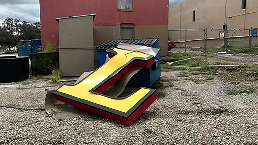 """Letters from Wells Fargo building sign found scattered. An """"L"""" was discovered propped against a dump"""