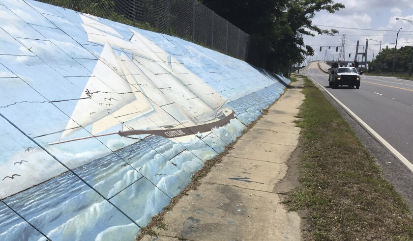 FILE - In this May 30, 2019, file photo, traffic passes a mural of the slave ship Clotilda along Africatown Blvd. in Mobile, Ala. The last slave ship known to have landed in the United States more than 150 years ago has a new owner: The state of Alabama. A federal judge granted ownership of the Clotilda shipwreck to the Alabama Historical Commission in a one-page order released Monday, April 13, 2020. (AP Photo/Kevin McGill, File)