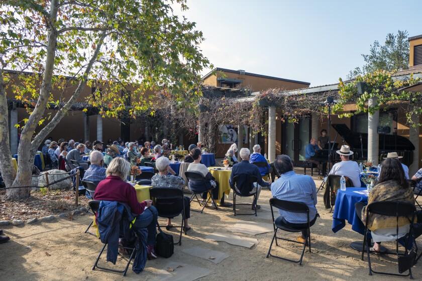Personas sentadas en sillas plegables al aire libre en el Centro Audubon en Debs Park escuchan a un pianista.