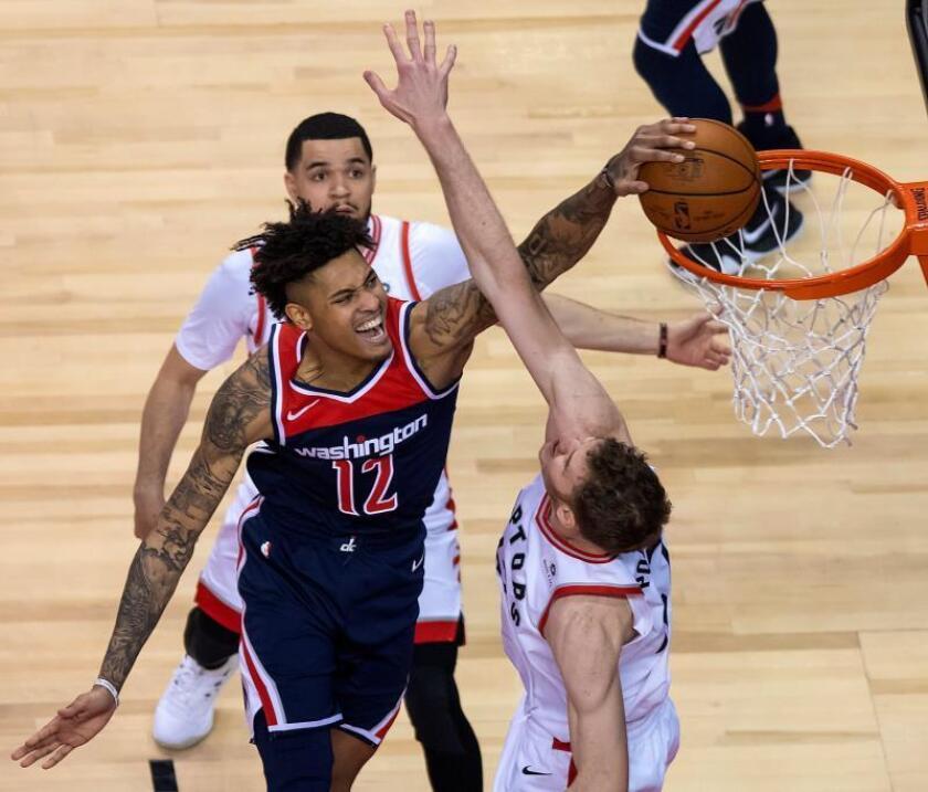 Kelly Oubre Jr. (i) de Washington Wizards clava el balón contra Fred VanVleet (atrás) y Jakob Poeltl (d) de Toronto Raptors durante su partido de la NBA de este martes. EFE