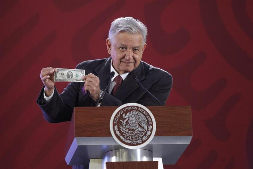 Mexican President Andres Manuel Lopez Obrador holds up a US $2 bill during his daily morning press conference on Friday, Jan. 4, in Mexico City. EFE-EPA/Sashenka Gutierrez