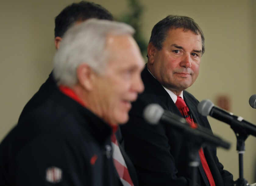 New San Diego State University head football coach Brady Hoke (right) listens as former head coach Rocky Long discusses his retirement.