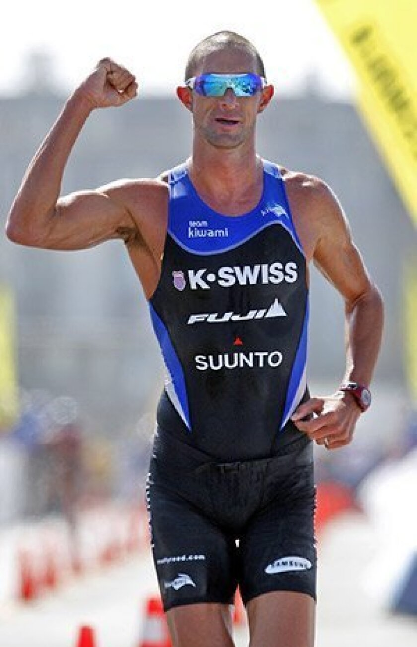 Matt Reed celebrates after rallying to win the Ironman 70.3 California in Oceanside. (K.C. Alfred / Union-Tribune)