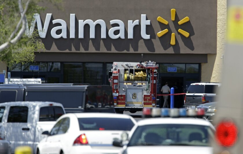 Police and firefighters appear on the scene of a shooting at a Walmart, Sunday, June 8, 2014 in Las Vegas. Police say two suspects shot two officers at a Las Vegas pizza parlor before fatally shooting a person and turning the guns on themselves at a nearby Walmart. (AP Photo/John Locher)