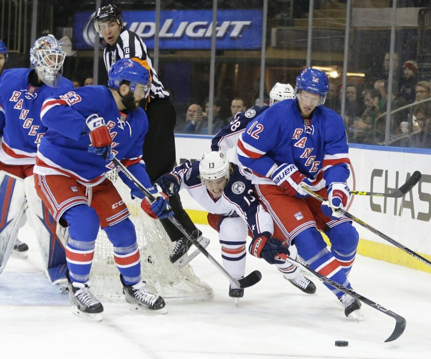 Referee Greg Kimmerly (18) avoids Columbus Blue Jackets' Cam Atkinson (13) as he fights for control of the puck with New York Rangers' Eric Staal (12) and Keith Yandle (93) during the first period of an NHL hockey game Monday, Feb. 29, 2016, in New York. (AP Photo/Frank Franklin II)