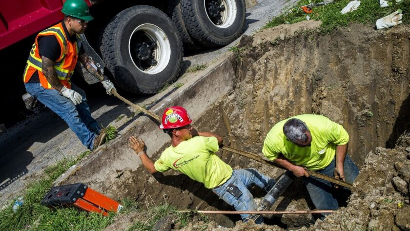 FILE- In an Aug. 31, 2016 file photo, crews break ground and work to remove and replace lead-tainted