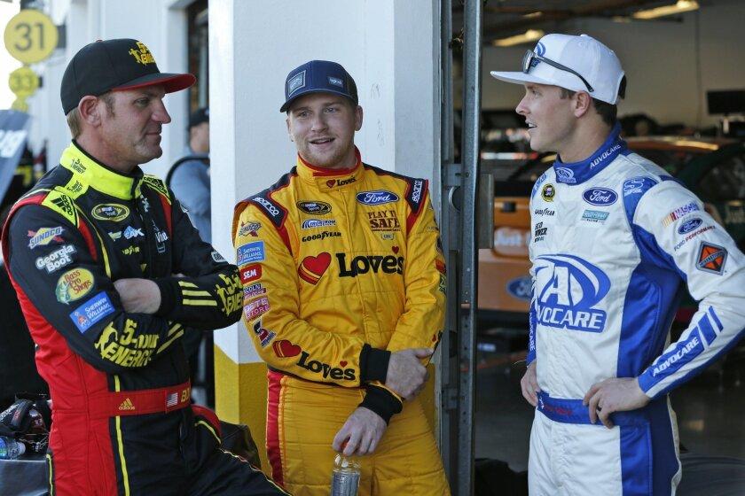 Clint Bowyer, left, Chris Buescher, center, and Trevor Bayne chat in the garage during practice for the NASCAR Daytona 500 auto race at Daytona International Speedway, Wednesday, Feb. 17, 2016, in Daytona Beach, Fla. (AP Photo/Wilfredo Lee)
