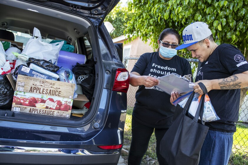 Stacy Rojas, right, and Dolores Canales of the Compton Bail Project check paperwork as they load supplies.