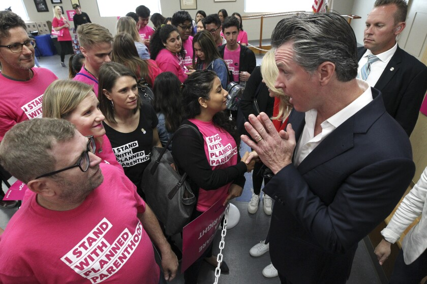 Gov. Gavin Newsom and his wife Jennifer Siebel Newsom meet supporters of Planned Parenthood after a rally at The United Food and Commercial Workers Local 135 building on Saturday in San Diego.