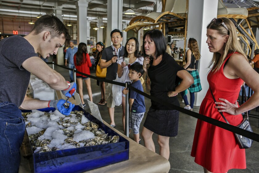 Kyle Fitz, left, shucks oysters as Erin Blayney, far right, Anne Trumble, second from right, and others watch at DTLA Oyster Festival at Grand Central Market in Los Angeles.