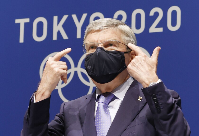 IOC President Thomas Bach gestures during a press conference at the Main Press Center, ahead of the Tokyo 2020 Olympic and Paralympic Games in Tokyo, Saturday, July 17, 2021. The first resident of the Olympic Village has tested positive for COVID-19, Tokyo Olympic organizers said on Saturday.(Shinji Kita/Kyodo News via AP)