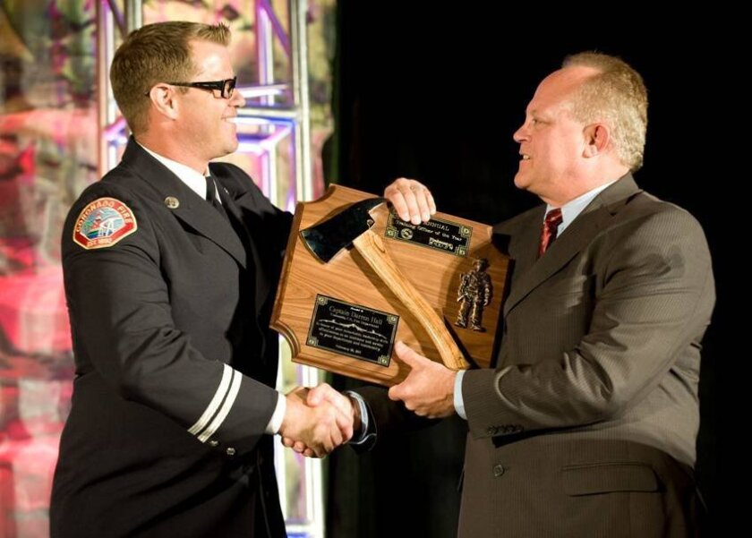 Steve Wilson, southern director of the California State Firefighters' Association, right, presents the group's Training Officer of the Year Award to Coronado Fire Capt. Darren M. Hall, during ceremonies Feb. 28 at the Firehouse World conference at the San Diego Convention Center.