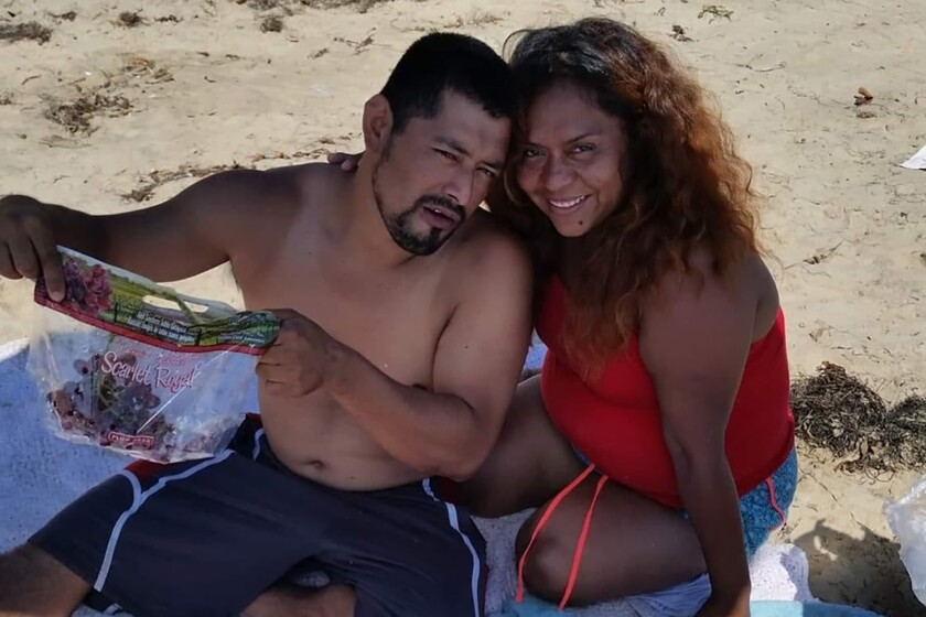 Long Beach couple smile while sitting on blanket in the sand.