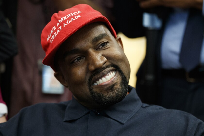 """Kanye West wears a red hat with Trump's """"Make America Great Again"""" slogan."""